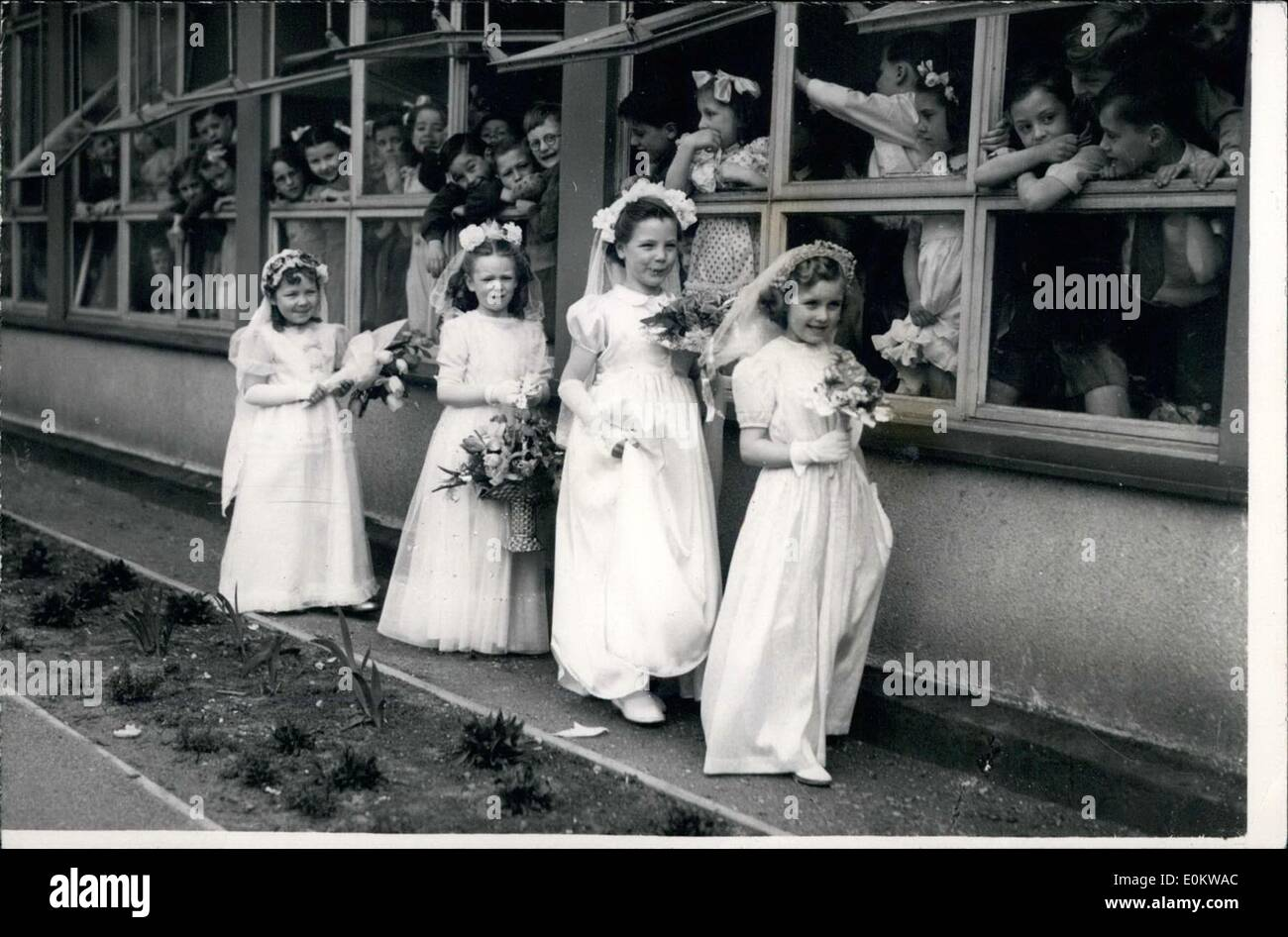 May 05, 1950 - May Day Ceremonies At The Hugh Myddleton School The Youngsters Look On: Photo shows Four of the tiny May Queens walk off as some of their school colleagues look on - during the May Day ceremonies - held this morning at the Hugh Myddleton School, E.C.I. during which six little girls were crowned as ''Queens of the May' - Stock Image