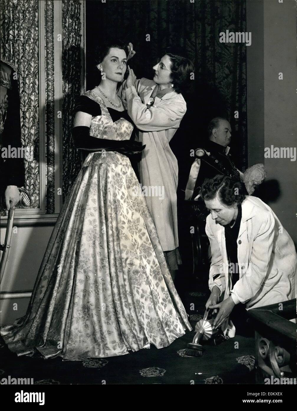 Jun. 06, 1952 - H.R.H. the duchess of Gloucester at Madame Tussaud's: Finishing touches are put to the hair of the Duchess of Gloucester by Miss Jean Fraser, assistant beautician at Tussand's, while Miss ''Scotty'' Hill vacuums the reproduction of the throne room carpet on which the figures of the new Royal group are placed. The Royal group at Madame Tussaud's: Latest attraction, ready for the Summer Season when thousands of foreign visitors explore its rooms filled with wax figures of the famous of the past and the present, is a new group of Royal figures - Stock Image