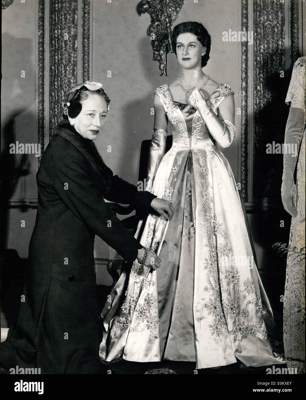Jun. 06, 1952 - Princess Margaret's new wax effigy at Tussaud's: Miss Denise of Norman Hartnell's adjusts the gown worn by the wax figure of H. R. R. Princess Margaret. which wear a ball gown similar to one she wore on her Carribean Tour. It is of honey - coloured satin, with a centre panel in a deeper tone down the centre. It is flared from the waist into a full skirt. The dress has delicate tracery of embroidery in beads and pailettes which empasize the two tones of the satin. Long matching gloves are worn, and the only jewellry is a single row of diamonds and small stud earrings - Stock Image