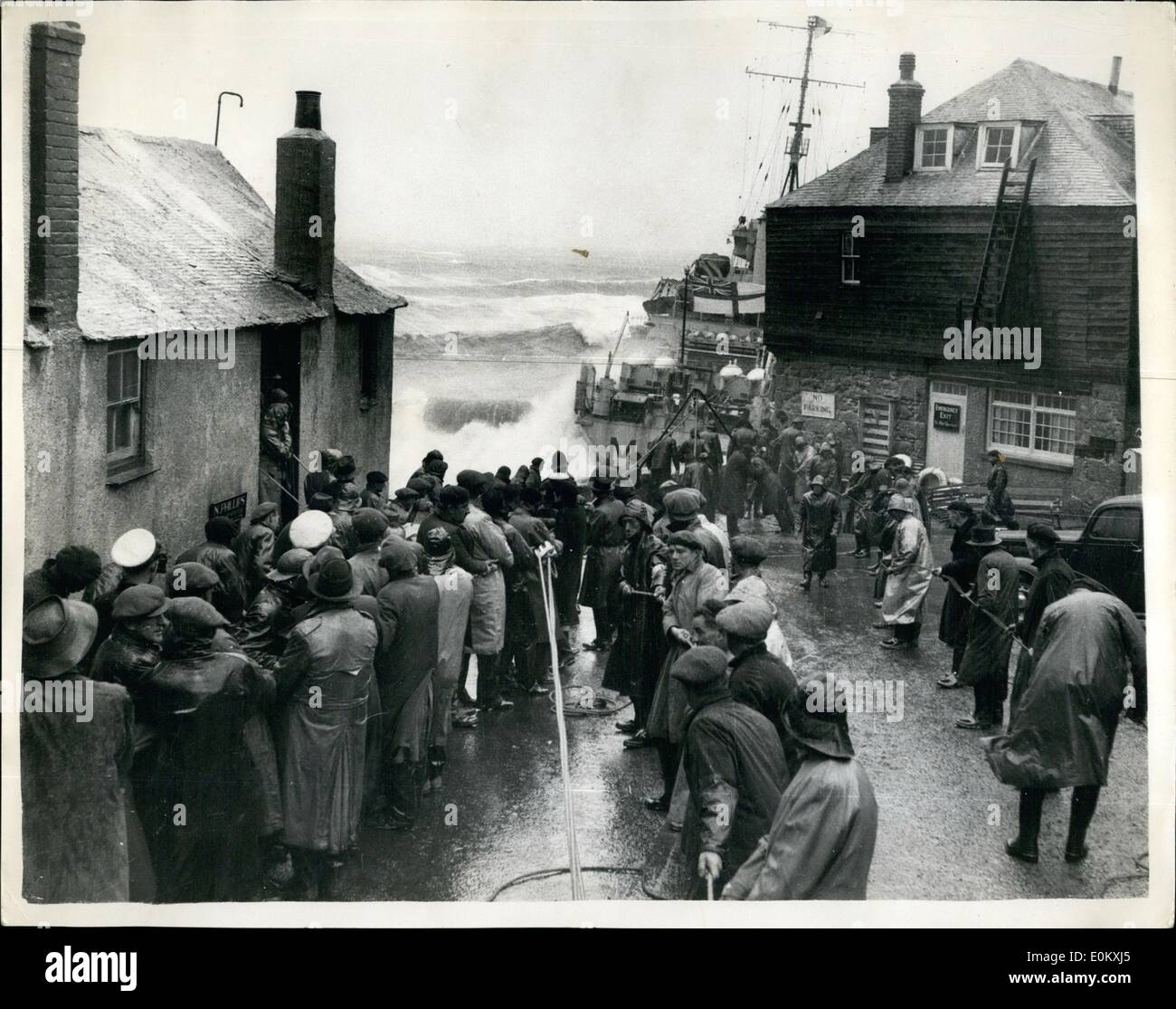 Oct. 10, 1952 - Ship On Rocks 20 Feet From Houses: Women and girls helped to rescue 62 men yesterday from 1,000-ton vesses, Wave, which was driven ashore by a gale at St. Ives, Cornwall. They hung on to the surging ropes while fishermen, policemen and shopkeepers hauled the men ashore by breeches buoy. Showers of oil from the ship swept over the quayside - and a doctor went among the drenched rescuers wiping it from their eyes. The Wave, a fishery protection vessel was driven on to the rocks only 20 feet from houses in the town - Stock Image