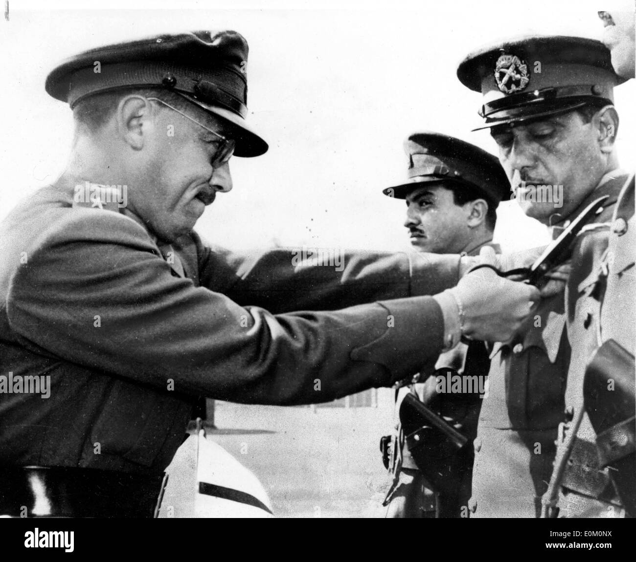 Feb 13, 1953; Cairo, Egypt; General Amer was sentenced to be stripped of his rank and Colonel Farah was acquitted. The charges were of desertion, inciting to revolt and trafficking in arms with Israel. General Amer was the officerwhom ex King Farouk tried to force last year into the presidency of the Officers' Club at Cairo. Gen. Amer was caught while trying to escape to Libya after the Neguib coup d'etat. The picture shows an officer stripping General HUSSEIN SIRRY AMER during the announcement of the Court Martial sentence in Cairo. - Stock Image