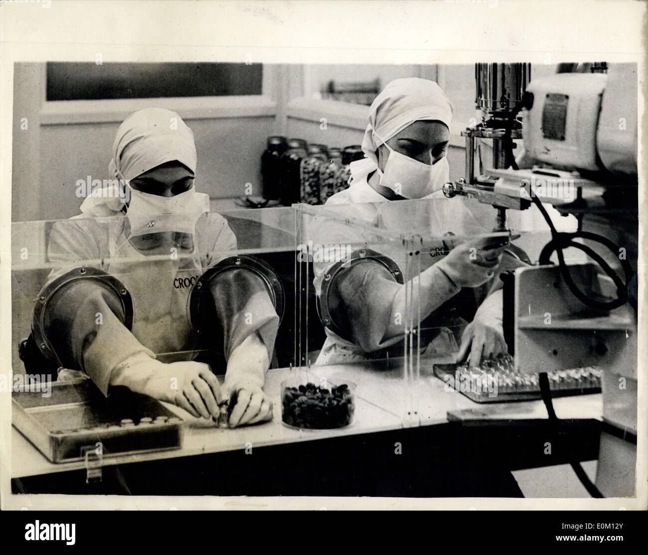 Feb. 19, 1953 - New Laboratory Opened: Mr. H.R. Mackeson, M.P. - the Overseas Secretary, yesterday performed the opening ceremony of the new Crookes Laboratories, at Park Royal. Mr. Mackeson had to don specially sterilised clothes - shoes - gloves and mask before entering one of the new pressurised aseptic ampoule filling rooms, where the air is filtered - to watch girls at work. The young ladies employed in this room have to be ''A.L.'' in health before they are allowed to work there. Photo Shows The Forbidden Room - Girls seen filling bottles with A.C.T.H - Stock Image