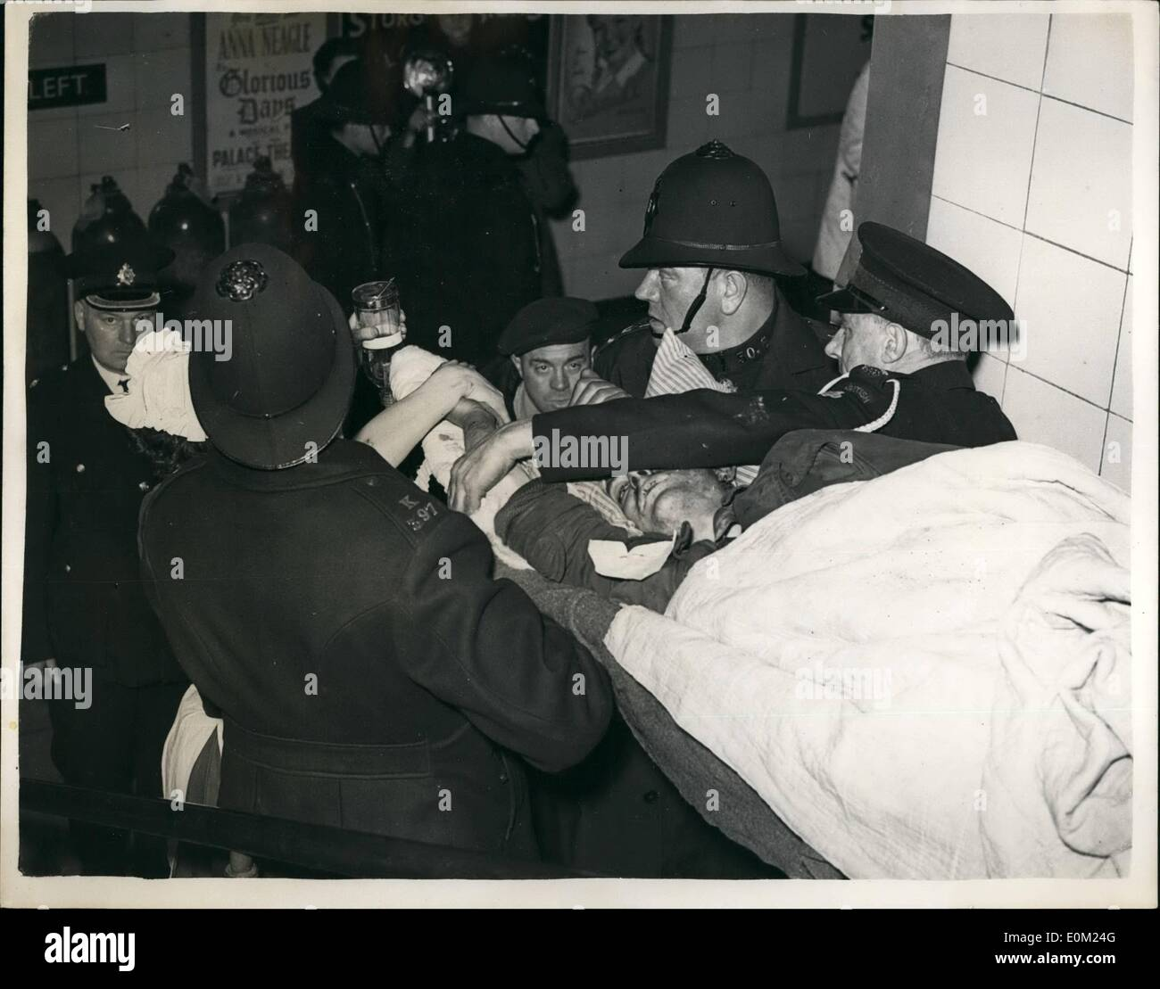 Apr. 04, 1953 - Nine Killed In Tube Disaster: Nine people were known today to have been killed in the Central Line tube disaster at Stratford last night - the worst in London's Underground history. Photo shows Ten hours after the crash policement and an ambulance men carry one of the inured out today. Stock Photo