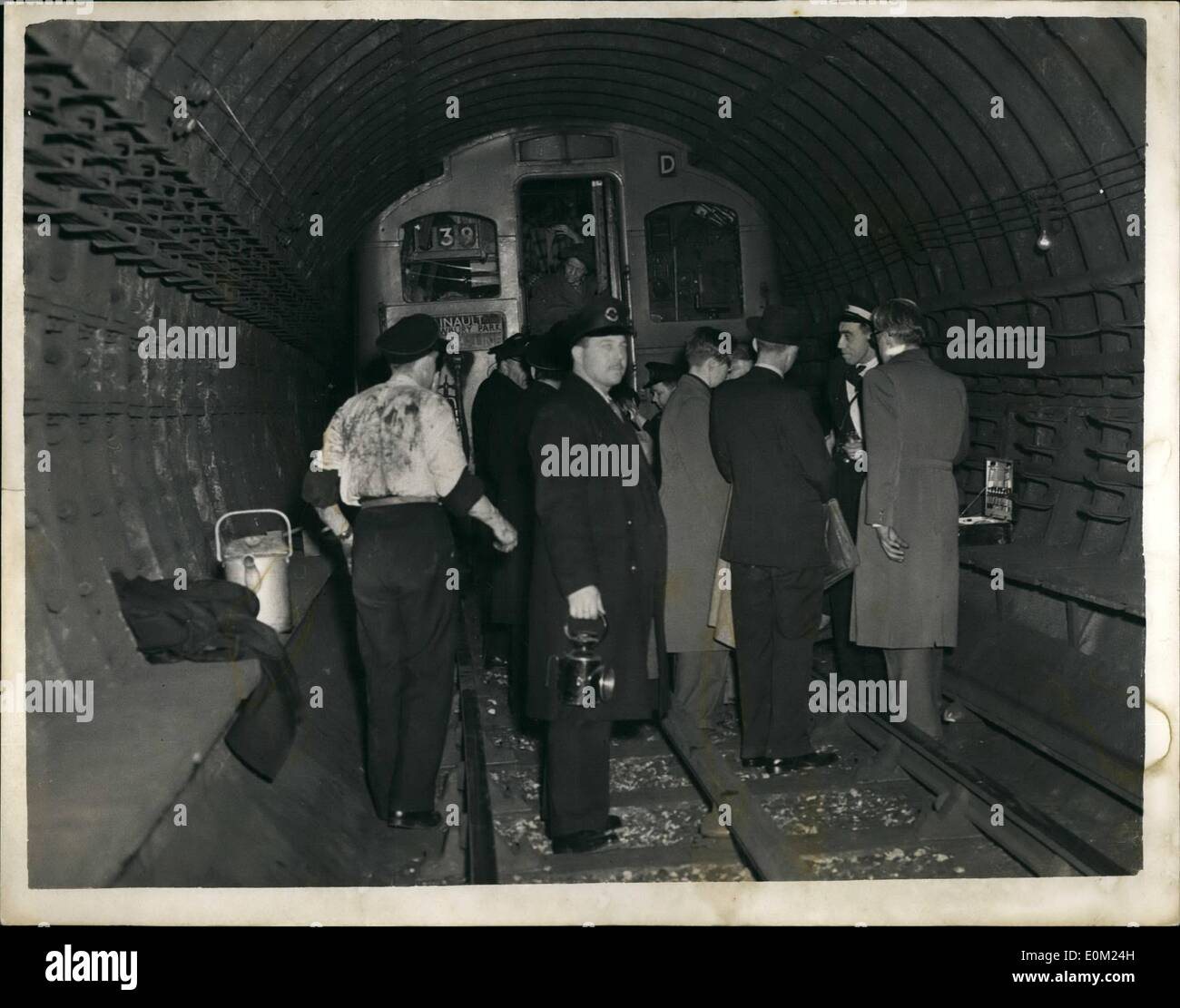 Apr. 04, 1953 - Nine dead in Tube disaster: Nine people were known today to have died in the Central Line tube disaster at Stratford last night the worst in London's Underground history. It was the second coach of the Baling Broadway Epping train which took the brunt of the crash. The train ran into the rear of another train travelling from Greenford to Hainsult. Photo shows last night's scene as railway officials help passengers from the rear of one of the coaches after the crash at Stratford - Stock Image