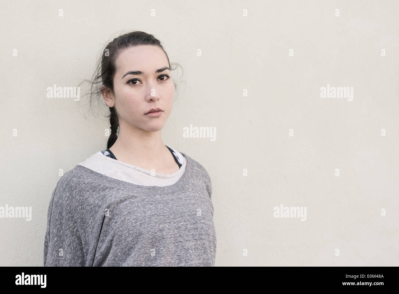 Portrait of young hispanic woman standing in front of wall. Pensive expression and looking at camera. - Stock Image