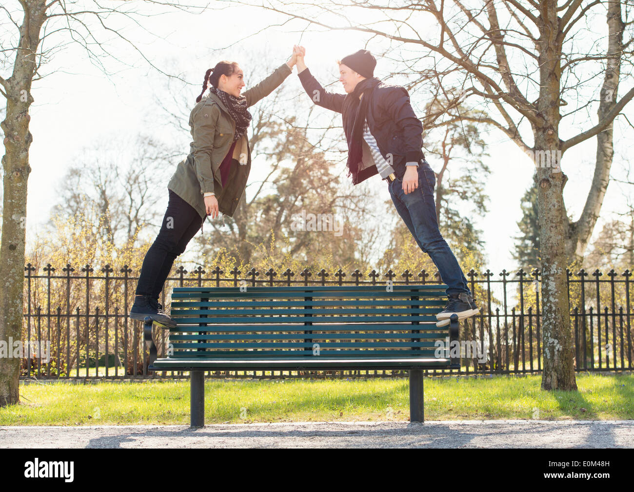 Dating young couple standing on park bench, holding hands. - Stock Image