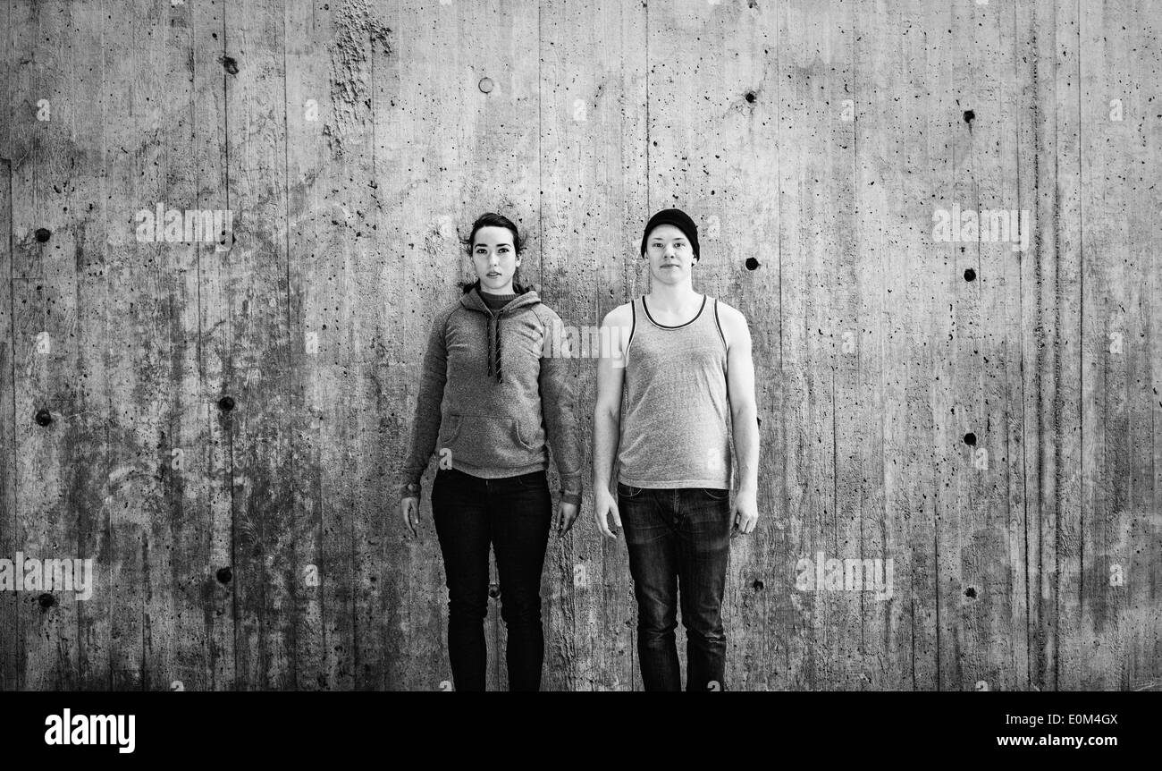 Portrait of young man and woman standing in urban area in front of concrete wall with copy space. - Stock Image
