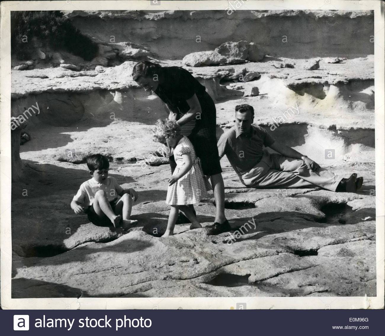 Apr. 04, 1954 - Royal Children in Malta: Lady Mountbatten lends a steadying hand as Princess Anne probes a tempting paddling pool. Elder brother Prince Charles dangles his feet into a pool unaided, but a watchful eye is kept on him by ''Uncle Dickie'' - Earl Mountbatten. Credit: Popperfoto - Stock Image