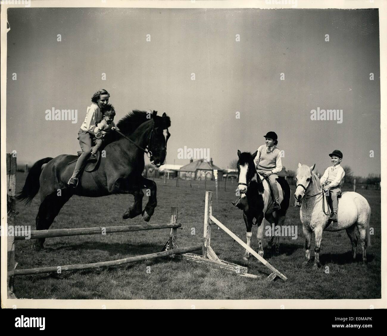 May 05, 1954 - Teaching Him Young: Little Phillip Payne thoroughly enjoys himself when his mother, Mrs. Lorna Payne, who was one of the famous ''Seven Sisters'' riding school - takes him over a jump with her. Keenly watching young Phillip's reactions, are his brother Barry, aged 9 - on his 9-year old pony ''High Jinks'', winner of over 150 prizes in Show Jumping, and his sister, Wendy, 16, herself an accomplished show jumper, riding her piebald jumper ''Barbary' - Stock Image
