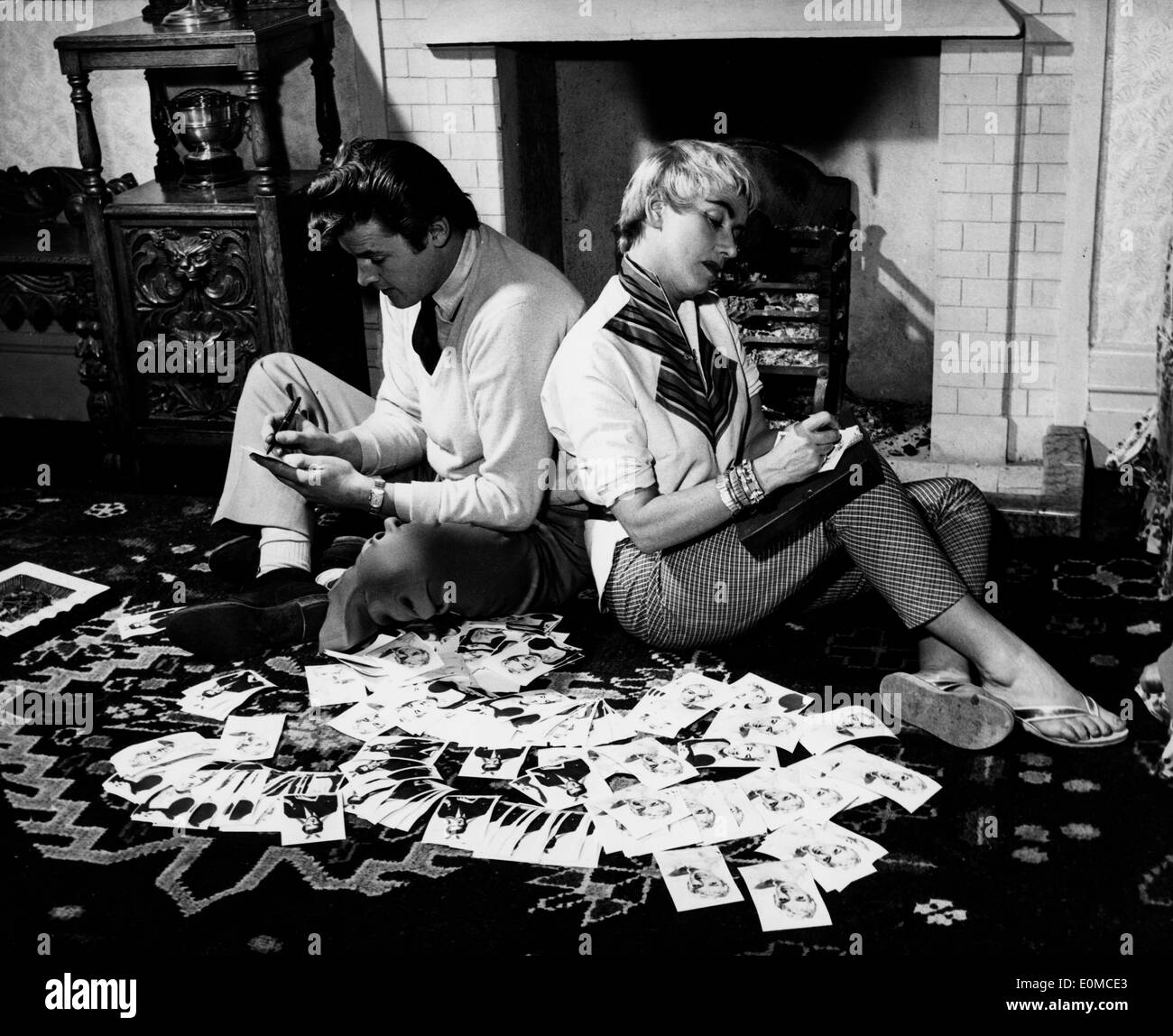 Actor Roger Moore and his wife Dorothy Squires surrounded by photographs - Stock Image