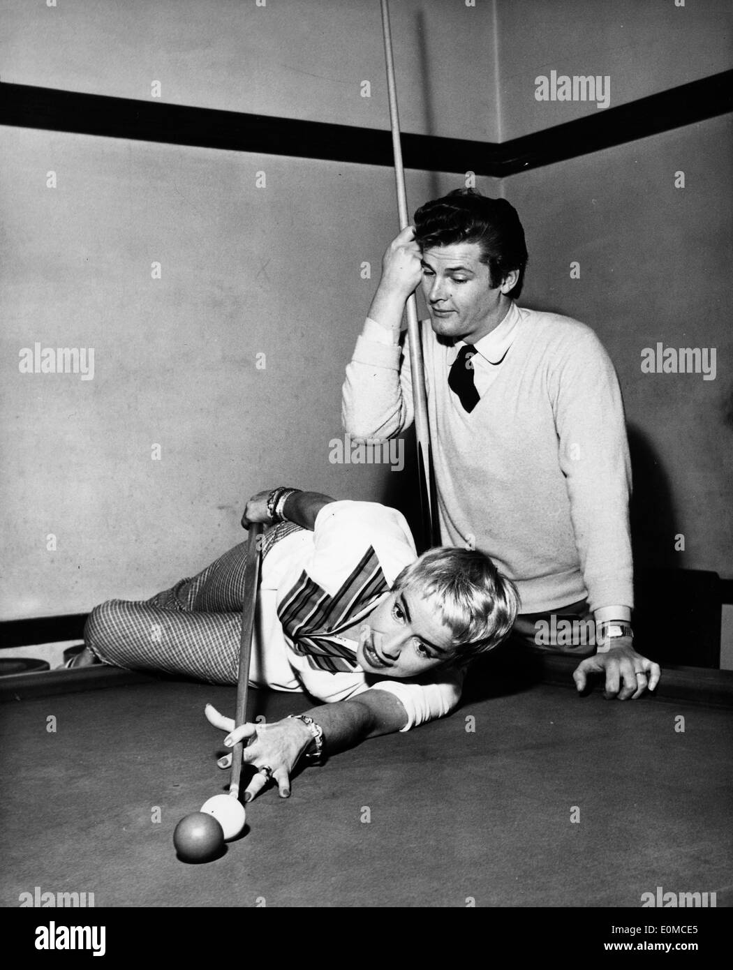 Actor Roger Moore and his wife Dorothy Squires playing pool Stock Photo