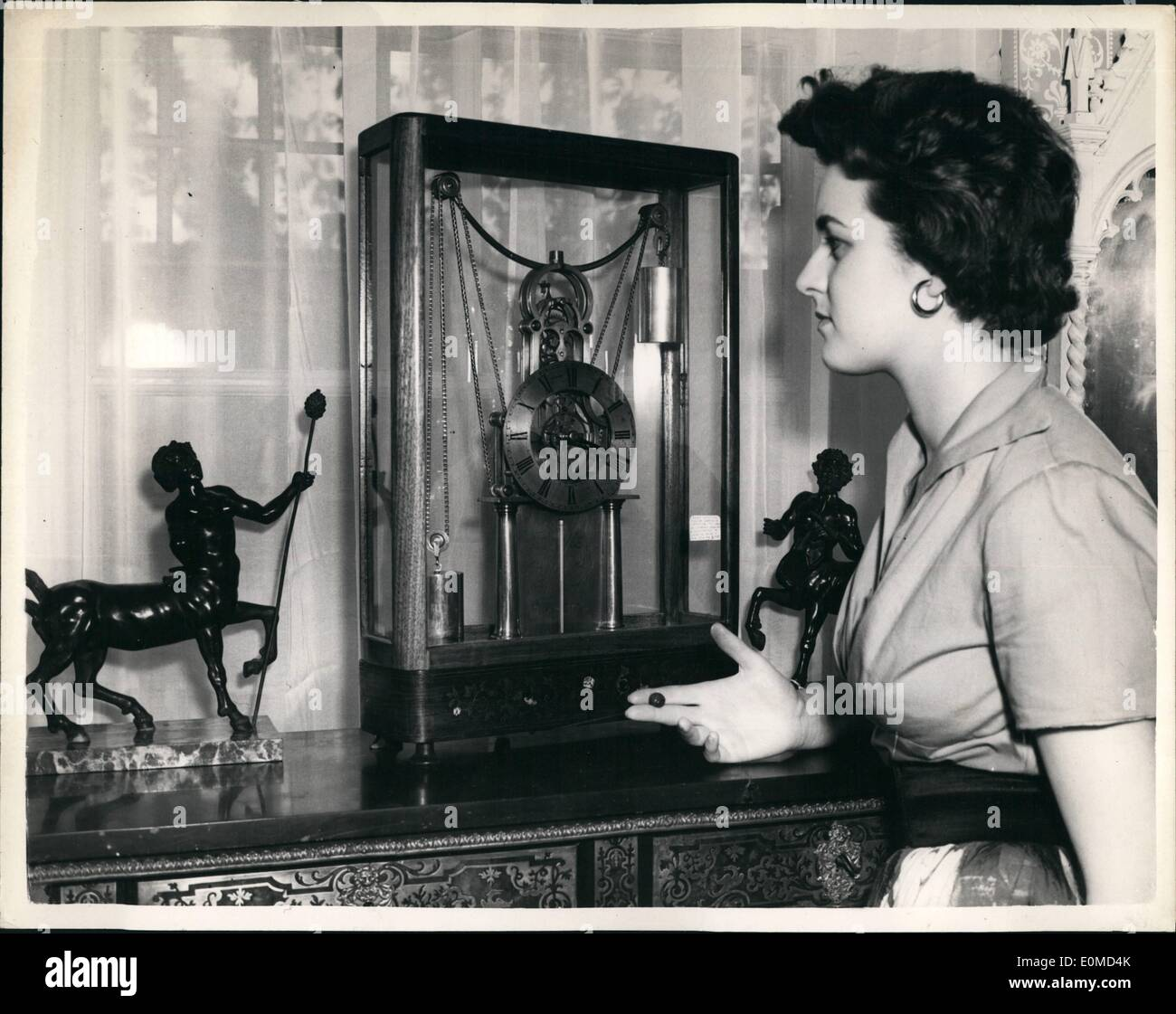 Sep. 09, 1954 - Autumn antique Dealer's Fair at Chelsea Town Hall. Needlework Chess Set. Press preview was held this afternoon at Chelsea Town Hall of the Autumn Antique Dealer's Fair. Keystone Photo Shows: Jacqueline Bromley admires a early American 19th century - 8 day skeleton mantel clock with thermometer below the dial. The clock is wound by cord underneath base. - Stock Image