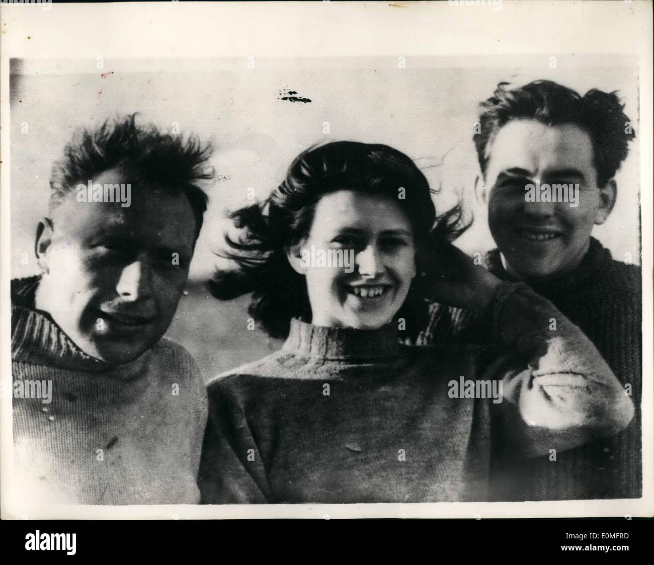 Mar. 03, 1955 - Three saved from sinking plane. Two men and a woman were saved from a sinking plane in a North Sea rescue last night. They were rescued by the Thames tanker, adaptivity, in heavy seas off Clacton - On sea. They were Mr. Leslie Anderson, Miss Sheila Martin and Mr. John Eadon who were returning in an Auster plane from a week-and in Paris, when they ran into bad weather, the tanker as he could. Photo shows Seen on board the Adaptivity, today are the three rescued week -and fliers - who in borrowed seaman's jerseys and dungarees, Mr. Leslie Anderson, Miss Sheila Martin and Mr - Stock Image