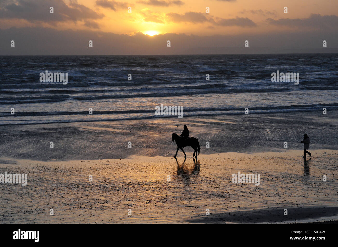 Horse and rider and pedestrian on Bracklesham Bay Beach. Sunset. - Stock Image