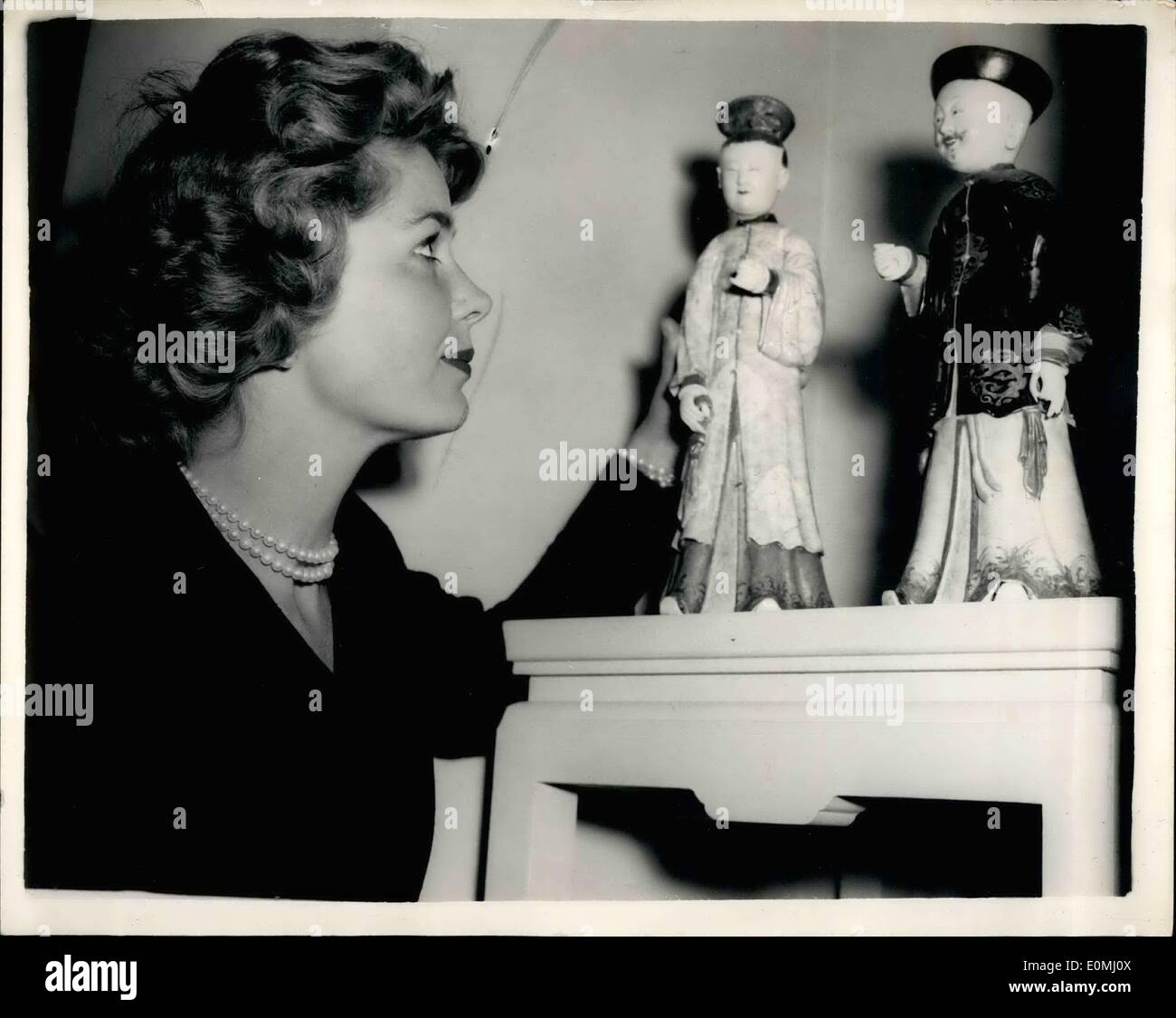 Jun. 06, 1955 - Antique Dealers' Fair Opens Tomorrow: The Antique Dealers' Fair and Exhibition, 1955, opens tomorrow in the Great Hall, Grosvenor House. Picture Shows: Mrs. Patricia Redford, examines a pair of Famille Rose Chinese figure (18th Century) - at today's preview. - Stock Image