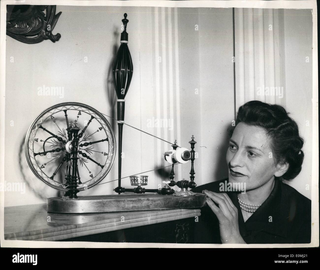 Jun. 06, 1955 - Antique Dealers Fair Opens Tomorrow: The Antique Dealers Fair and Exhibition 1955, opens tomorrow in the Great Hall, Grosvenor House. Photo Shows:- Miss Enid Morgan, of Criclewood, looking at the early Nineteenth Century French spinning-wheel, in gilt bronze, ivory and ebonised wood - at today's preview. - Stock Image