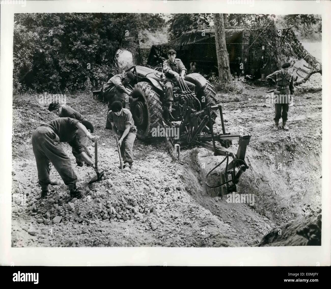 Sep. 09, 1955 - ATOMIC WARFARE DOES NOT OUTDATE SHOVELS: Soldiers past and present will be sorry to note that although twelve ''Dinkums'', new lightweight hydraulically-operated diggers, were used in a recent atomic warfare exercise of Britain's Territorial Army, shovels were also in evidence. But the Dinkums, each capable of shifting five cubic yards of earth an hour,did make possible the digging of a hole for an underground brigade headquarters in 1 1/2 hours. Into the hole end-on-end went two iron tubes 7 ft. 6 ins. in diameter. A topping of an 18-inch layer of sandbags completed the job - Stock Image
