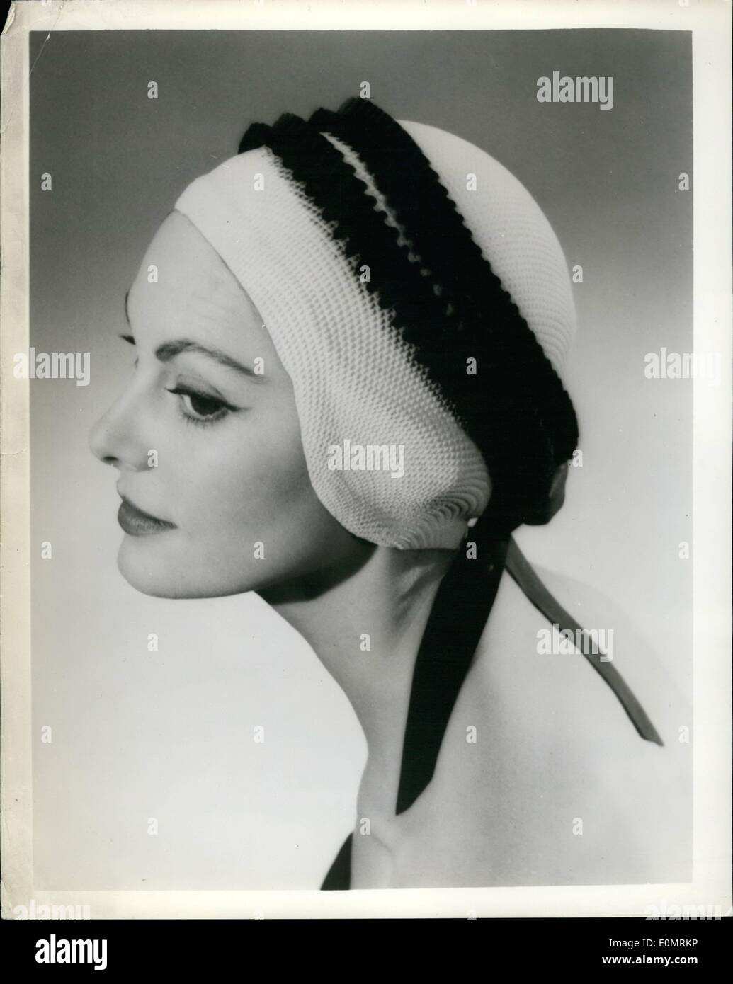 May 05, 1956 - Bathing duty - and Streetwear, too; From Britain is a bathing cap suggested as smart enough for streetwear on a rainy day. An inner rubber flange makes it water tight and it has been specially designed to prevent hair drag. Photo Shows: The ''Viking'' cap, made in white trimmed with red, blue, yellow. - Stock Image