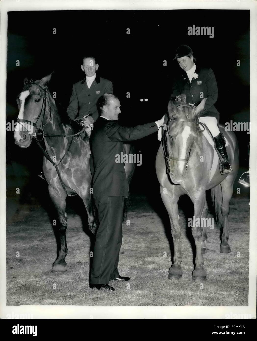 Jul. 24, 1956 - 24-7-56 Duke of Edinburgh presents a whip to Pat Smythe. H.R.H. The Duke of Edinburgh last evening visited the International Horse Show at White City where he presented a presentation whip to each member of the British Show Jumping Team, Wilf White; Pat Smythe and Peter Robeson, who won the bronze medal at the recent Stockholm Equestrian Olympics. Keystone Photo Shows: The Duke of Edinburgh presents the whip to Pat Smythe at the White City while Wilf White looks on last evening. - Stock Image