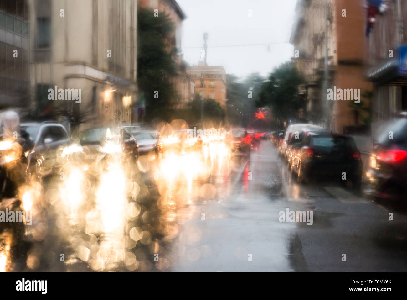 blurred light of cars seen through  a wet windshield with some raindrops on it in the early morning of a rainy day - Stock Image