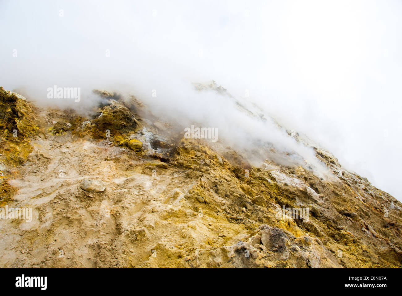 on the top of etna volcano the rock is covered with sulphur and became yellow, cloud of toxic gas spread from the crater - Stock Image