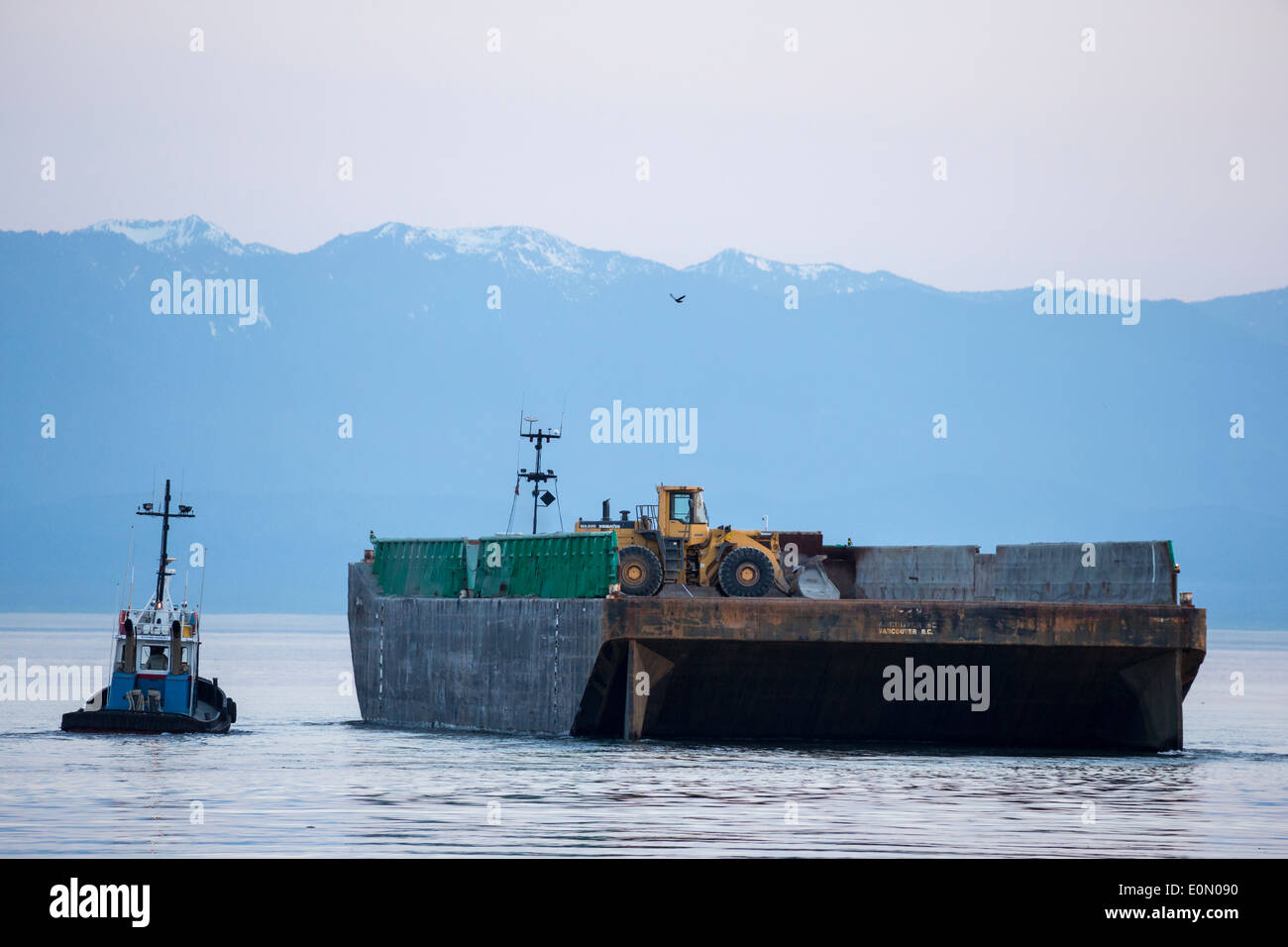 Tugboat and heavy duty equipment barge at dusk-Victoria, British Columbia,Canada. - Stock Image