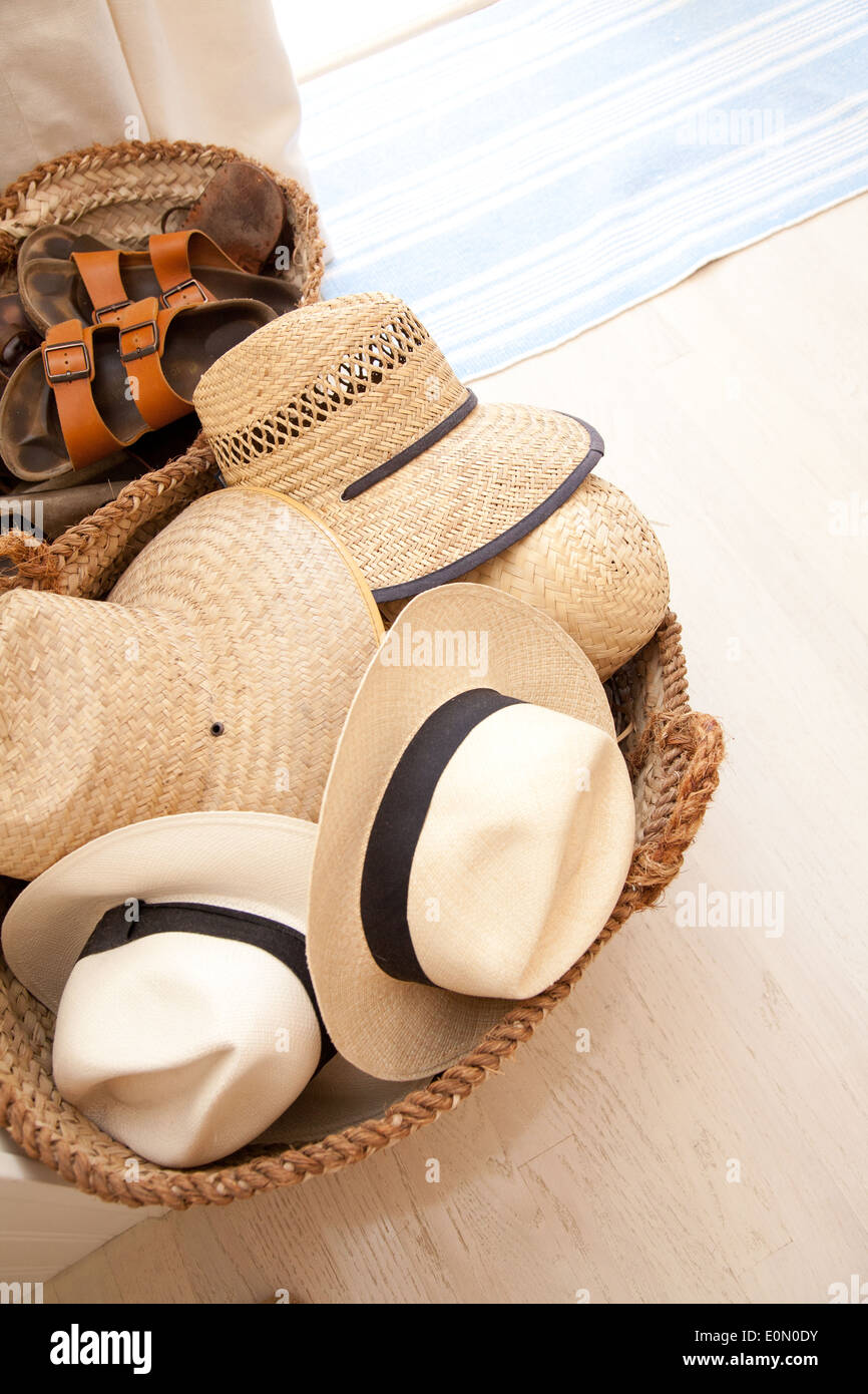 Basket of straw hats and sandals on light wood floor. - Stock Image
