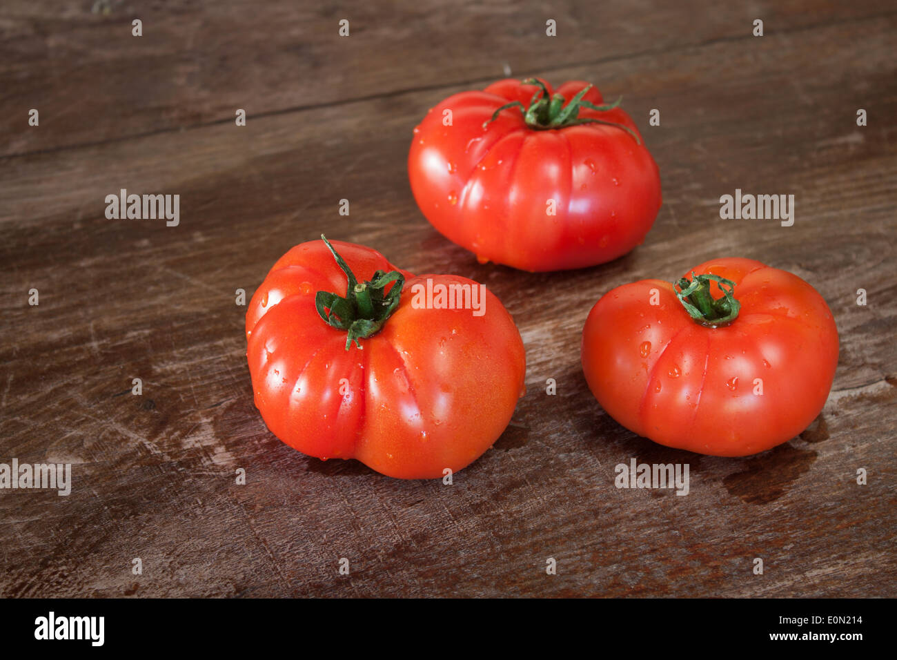 tomato wood wooden table closeup - Stock Image