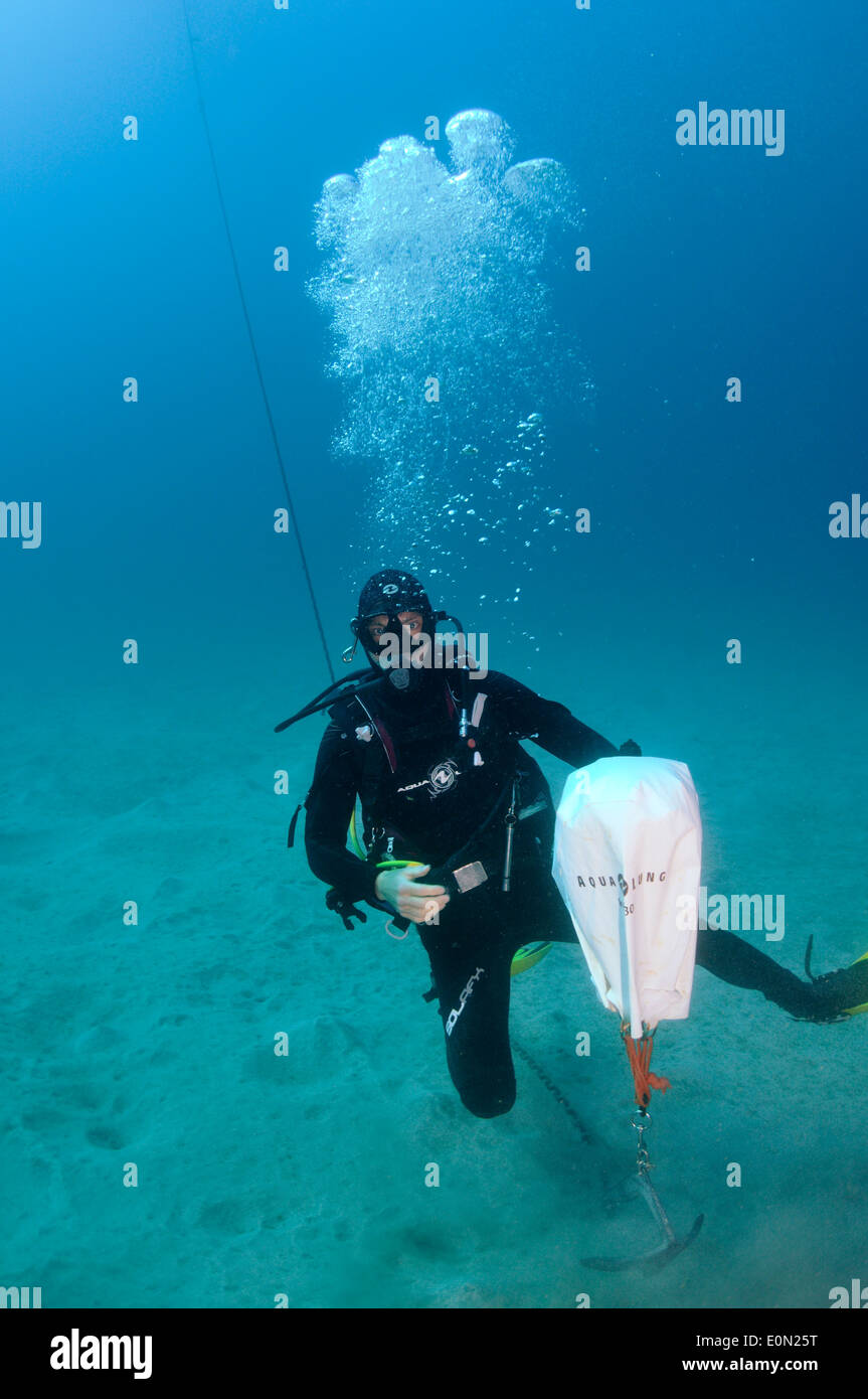 Scuba diver on sandy seabed setting up lifting bag to lift anchor Stock Photo