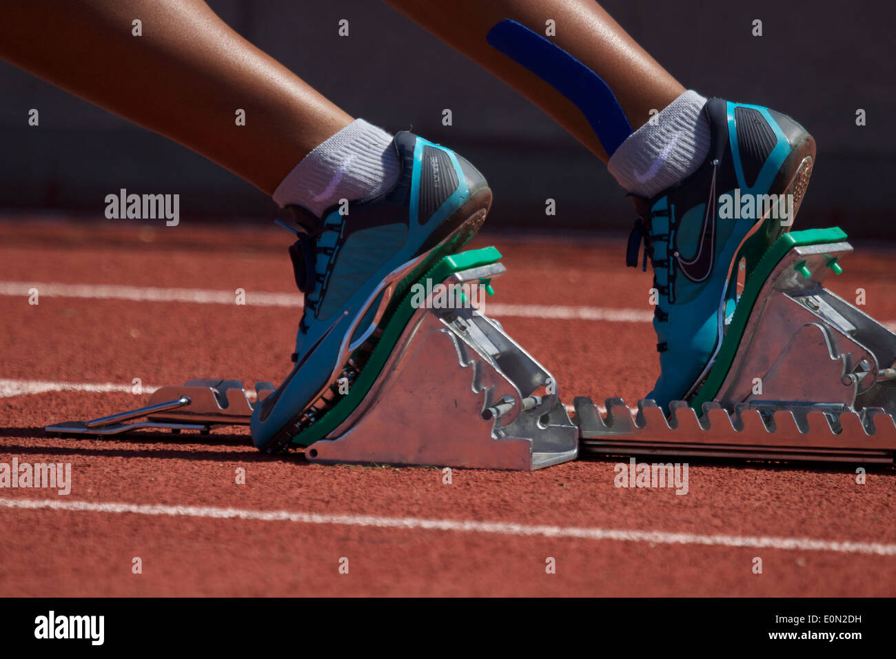 Female African American runners feet in a set of Starting blocks on a running track start line California USA - Stock Image