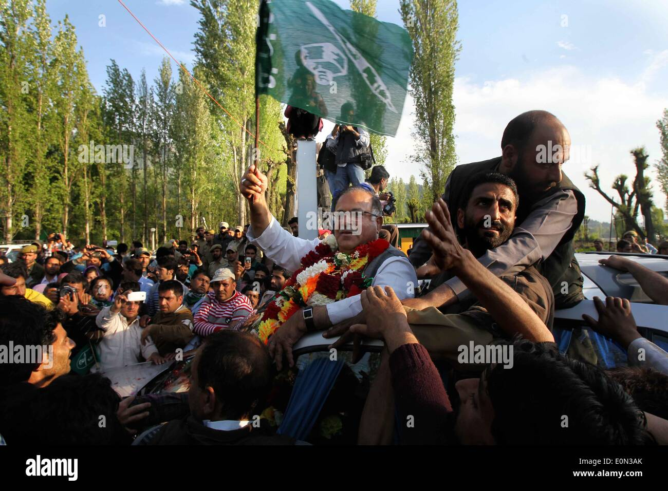 Srinagar, Indian-controlled Kashmir. 16th May, 2014. Tariq Hamid Kara, leader of Indian controlled Kashmir's main opposition party Peoples Democratic Party (PDP), holds a party flag as people greet him after he was declared winner for a parliamentary seat, in Srinagar, the summer capital of Indian-controlled Kashmir, May 16, 2014. The region's main opposition Peoples Democratic Party (PDP) and right-wing Hindu nationalist Bhartiya Janta Party (BJP) Friday swept polls by winning three seats each in the region, officials said. Credit:  Javed Dar/Xinhua/Alamy Live News - Stock Image