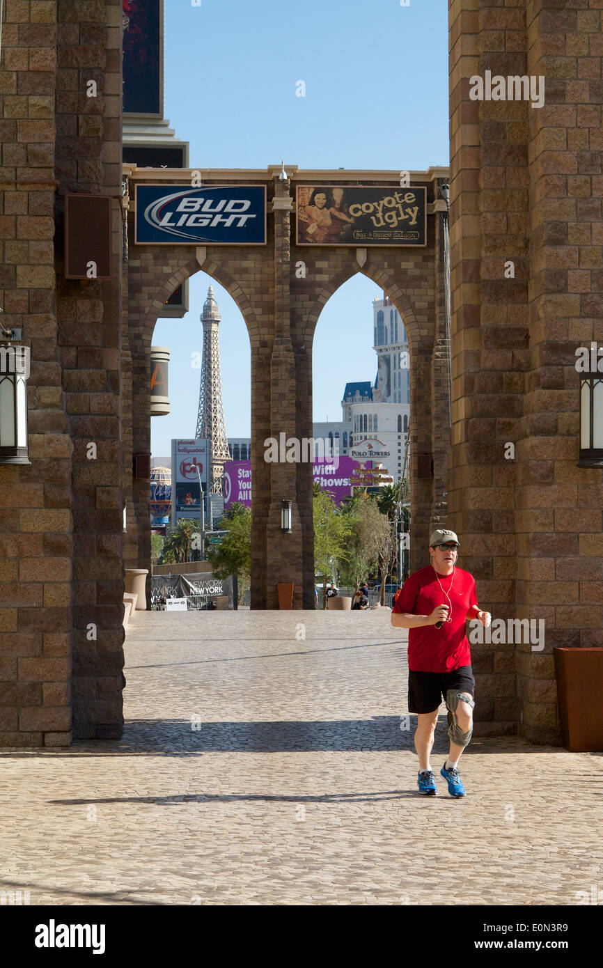 Man jogging with a knee brace over a replica of the Brooklyn Bridge on the Las Vegas strip early morning - Stock Photo