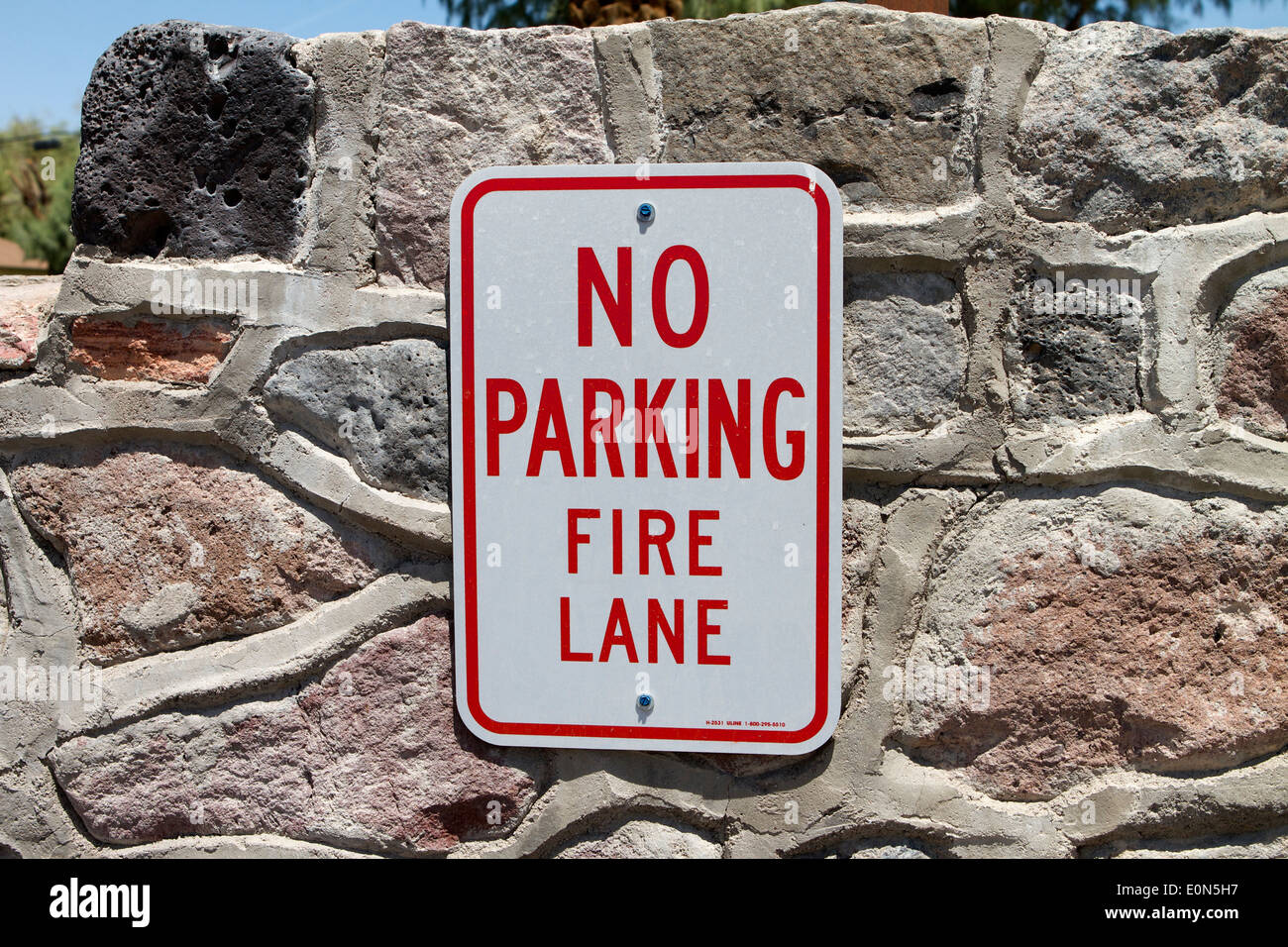 No Parking Fire Lane sign on a natural stonewall - Stock Image