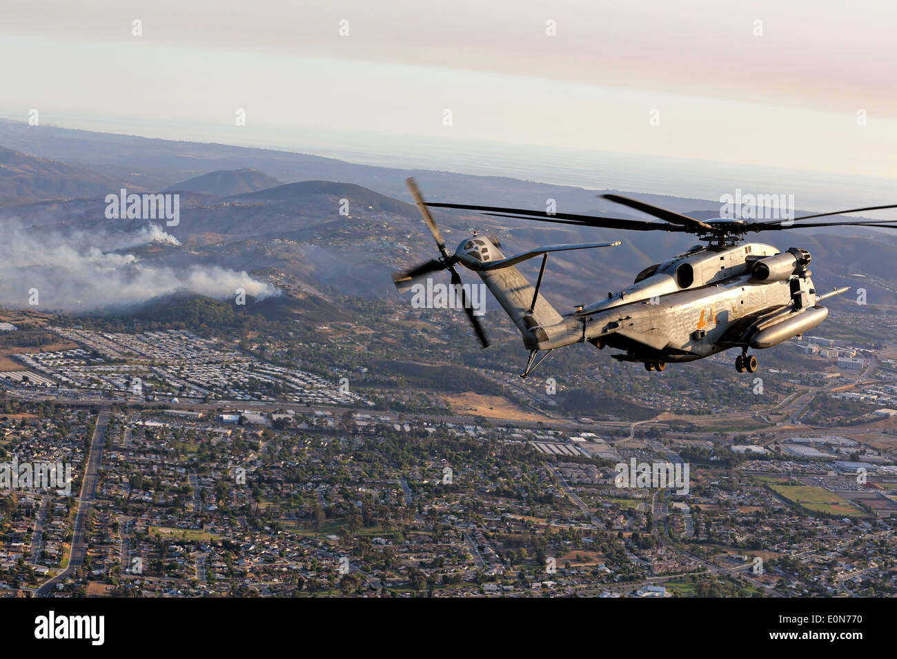 A US Marine Corps CH-53D Sea Stallion helicopter approaches the Cocos wildfire to assist in firefighting May 15, 2014 around San Marcos, California.  Evacuations forced more than 13,000 people from their homes as the fire burned across San Diego County. Stock Photo