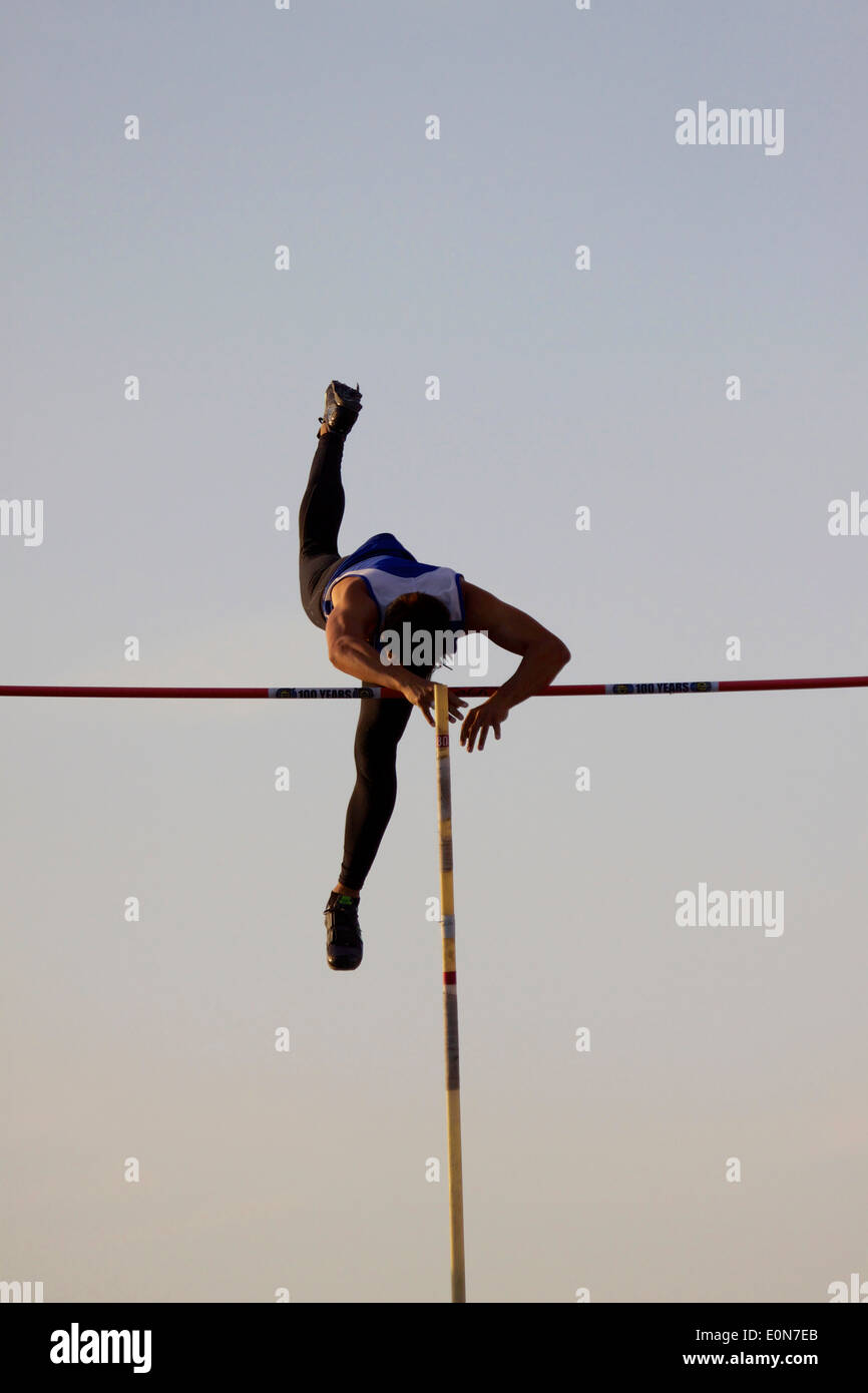 A male pole vaulter clears the bar - Stock Image