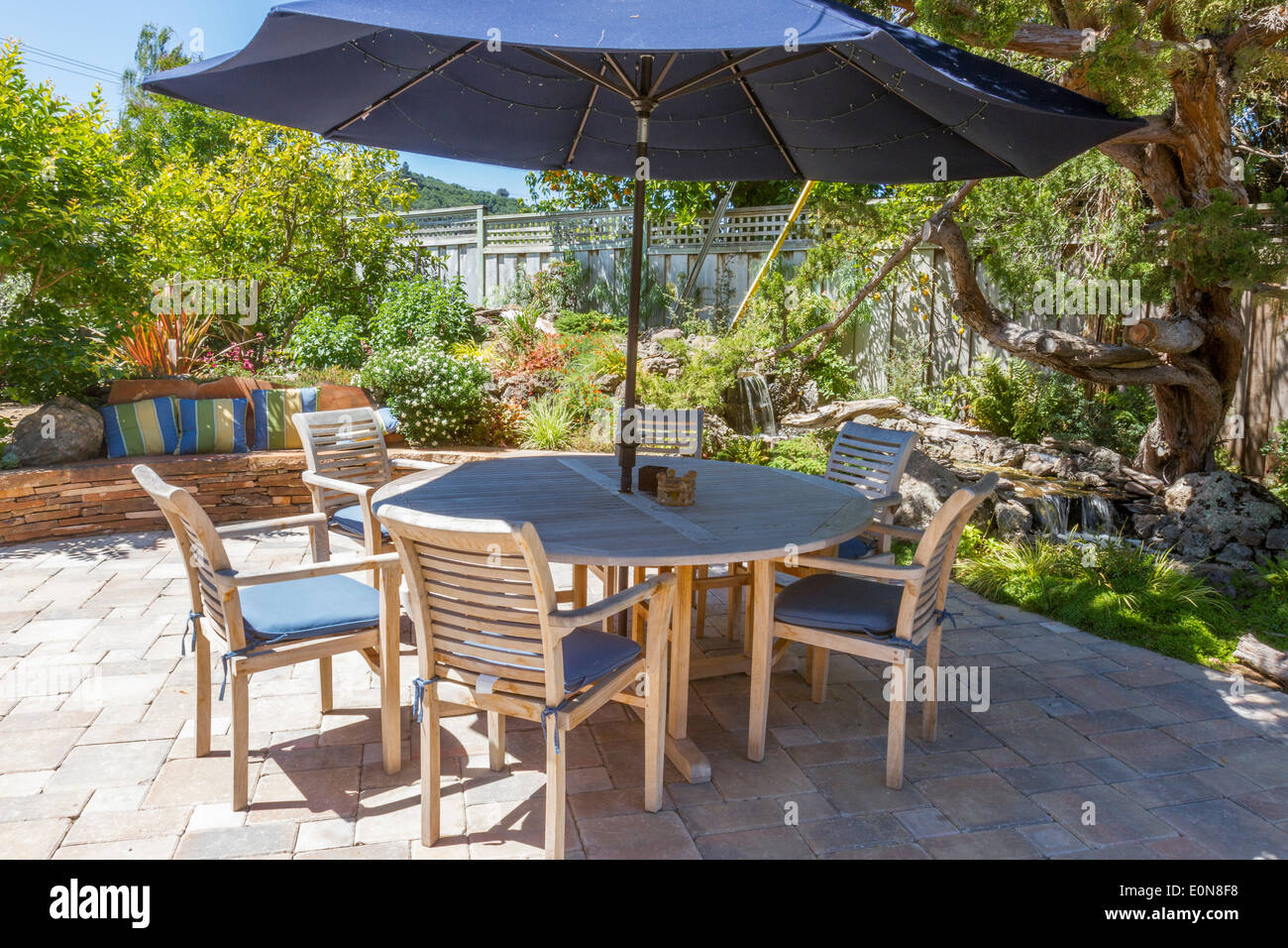 Beautiful backyard landscaping with stream water feature behind patio dining table - Stock Image