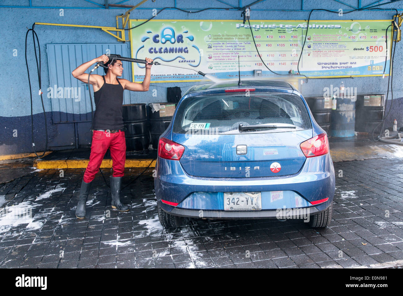 young Mexican man moves like a dancer as he washes a shiny blue Ibiza hatchback luxury car by hand at a Mexico City car wash - Stock Image