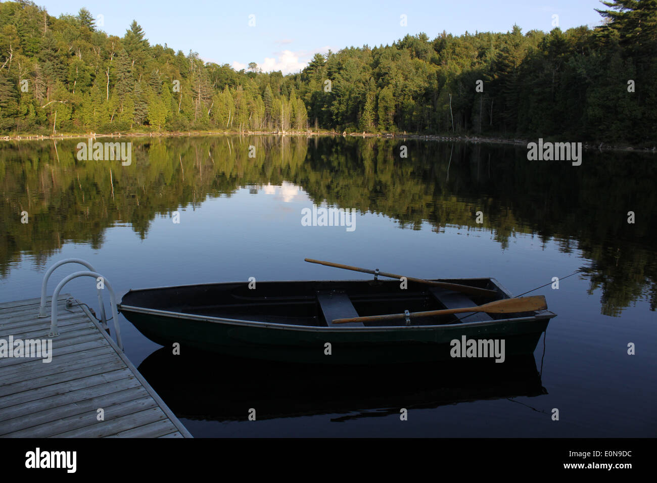 Docked row boat on a small lake in cottage country in Quebec, Canada - Stock Image
