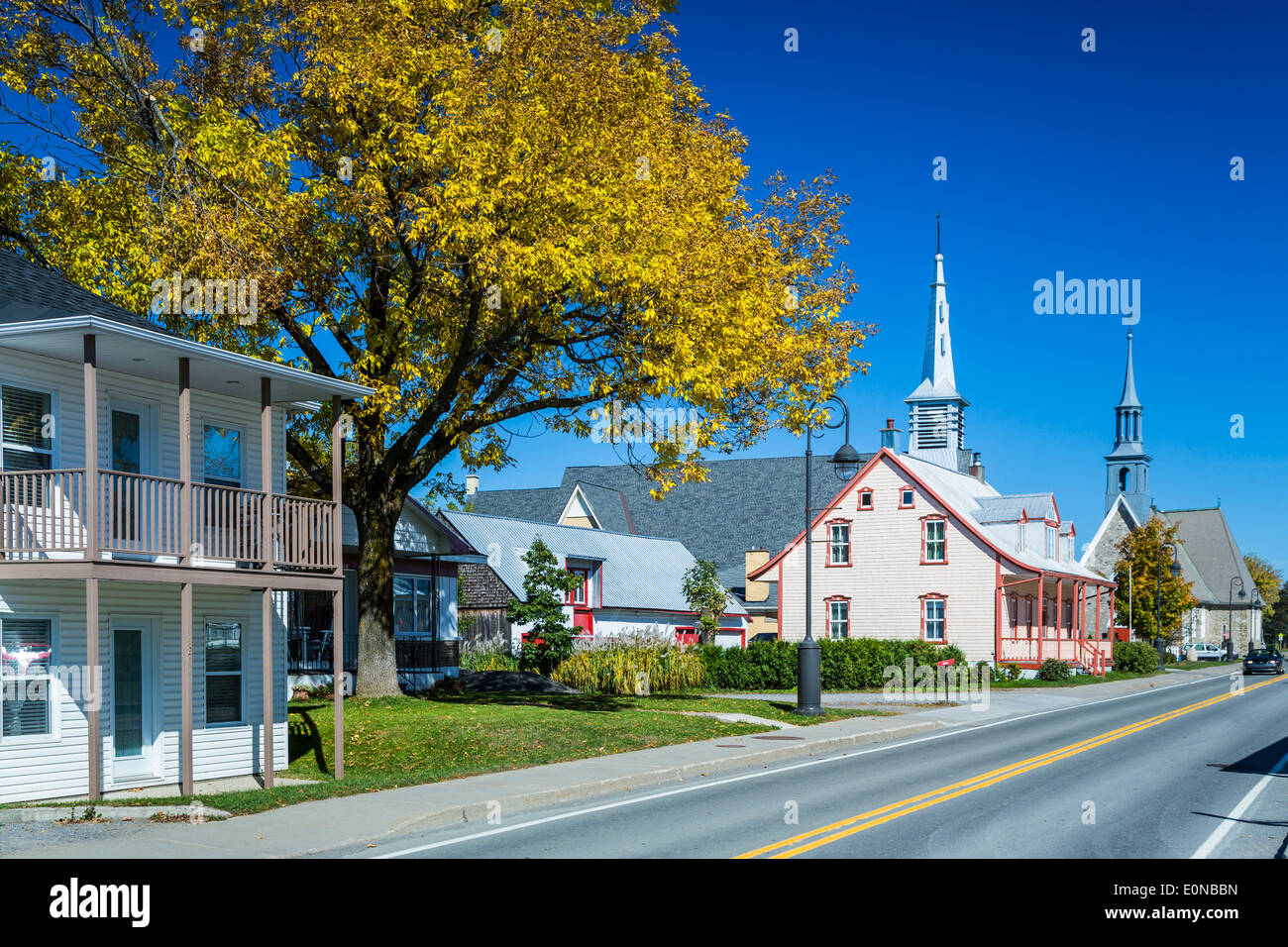 A street with homes and a church in the village of Saint Pierre on the island of Ile d' Orleans, Quebec, Canada. - Stock Image