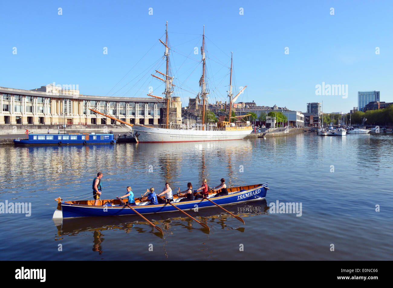 Bristol, UK. 17th May, 2014. Early morning rowers seen passing  a Tall Ship seen in the back ground of the Floating Harbour in the City of Bristol in the UK, as the sun rises to a wonderfull day ahead. Forecasters are predicting warm and sunny weather for the weekend. Credit:  Robert Timoney/Alamy Live News - Stock Image