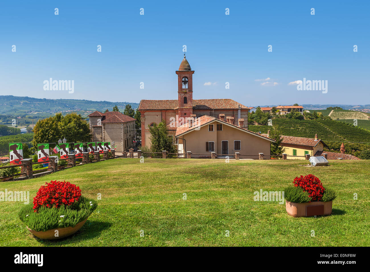 Green lawn in front of small rural church under blue sky in Piedmont, Northern Italy. - Stock Image