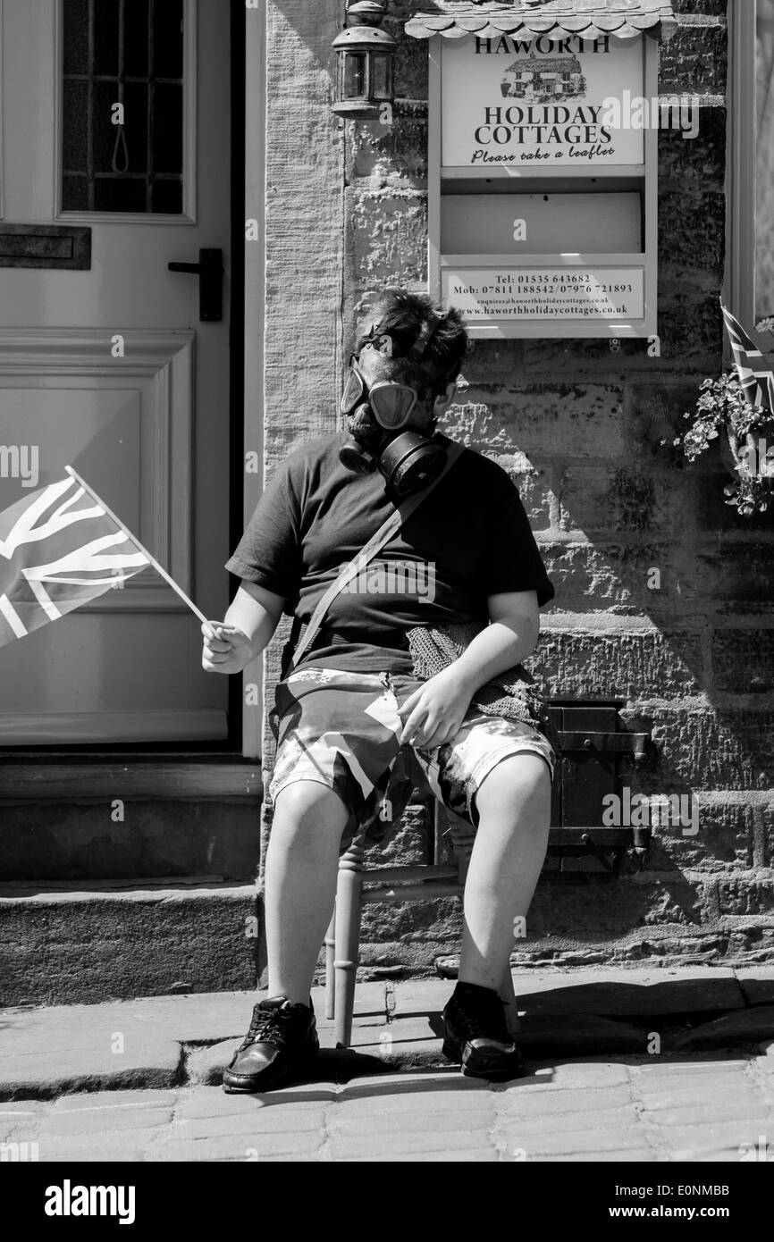 Haworth, West Yorkshire, UK. 17th May 2014. A young boy sits outside a house wearing a war-time gas mask. Haworth, a small village in the city of Bradford in West Yorkshire has held the first day of its 1940s weekend on Saturday, March 17, 2014. Good weather brought hundreds into the village for this event where locals and visitors don wartime attire. Credit:  Christopher Middleton/Alamy Live News - Stock Image