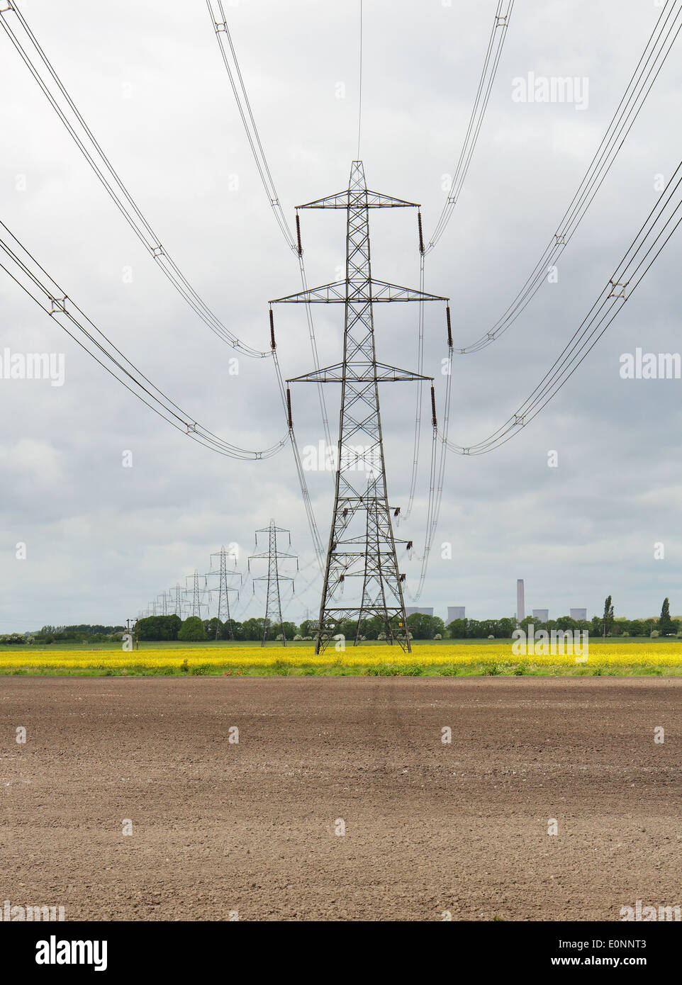 An English Landscape with electricity Pylons with Power Station in the distance and field of yellow rapeseed - Stock Image