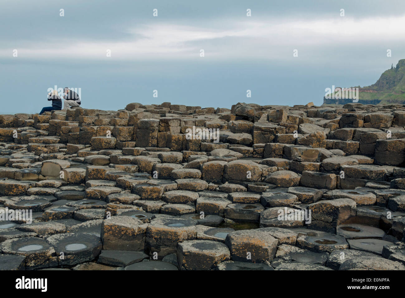 Couple sitting on the basalt stones at the Giant's Causeway, County Antrim, Northern Ireland, UK, a UNESCO World Heritage Site. - Stock Image