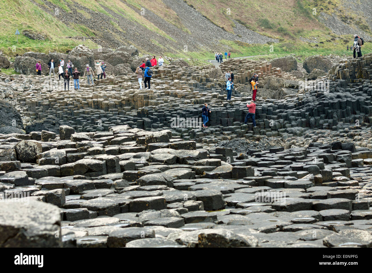 Tourists exploring the Giant's Causeway, County Antrim, Northern Ireland, UK, a famous UNESCO World Heritage Site. - Stock Image