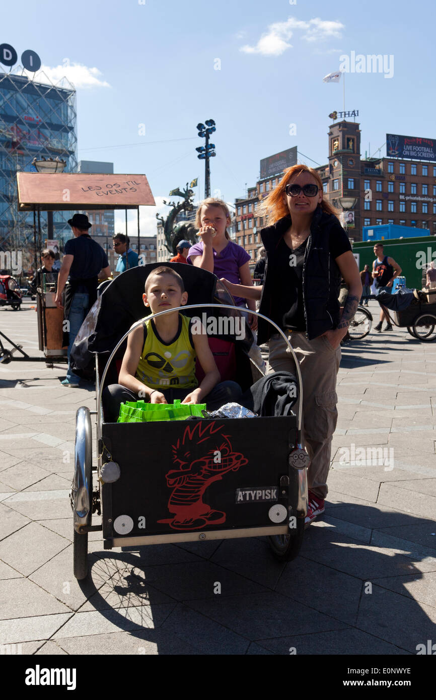 """Copenhagen, Denmark – May 17th, 2014: """"This is the way we move around as a family here in the inner city because it's easy and safe,"""" says Ziga (left), mother to Rebecca 5 years (middle)and Casper, 9 years (left) about here 3 wheeled Christiania bike. Together with many other enthusiast for this special bike they celebrated the 30 years anniversary of Free Town Christiania's iconic cargobike, which in 2011 received Danish Design Center's  award by his Majesty, Danish Crown Prince Frederik. - Stock Image"""