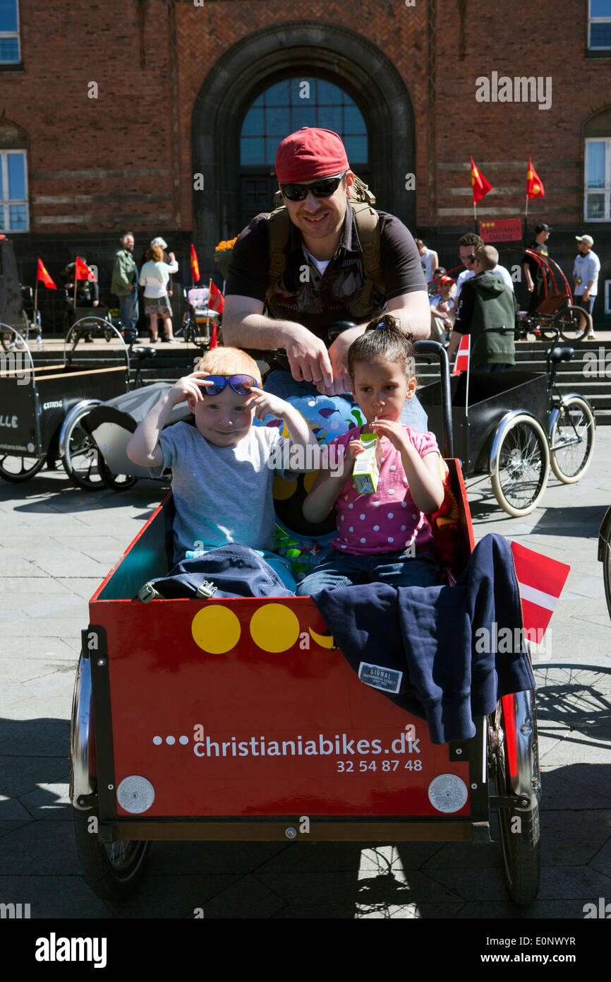 Copenhagen, Denmark – May 17th, 2014: A little family with their Christiania cargobike. Together with many other enthusiast for this special bike they celebrated the 30 years anniversary of Free Town Christiania's iconic bike, which in 2011 received Danish Design Center's  award by his Majesty, Danish Crown Prince Frederik. - Stock Image