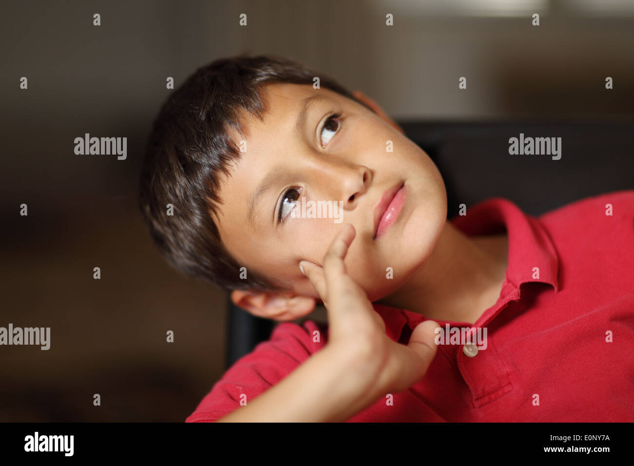 Boy thinking or day dreaming when doing homework - with very shallow depth of field and copy space - Stock Image