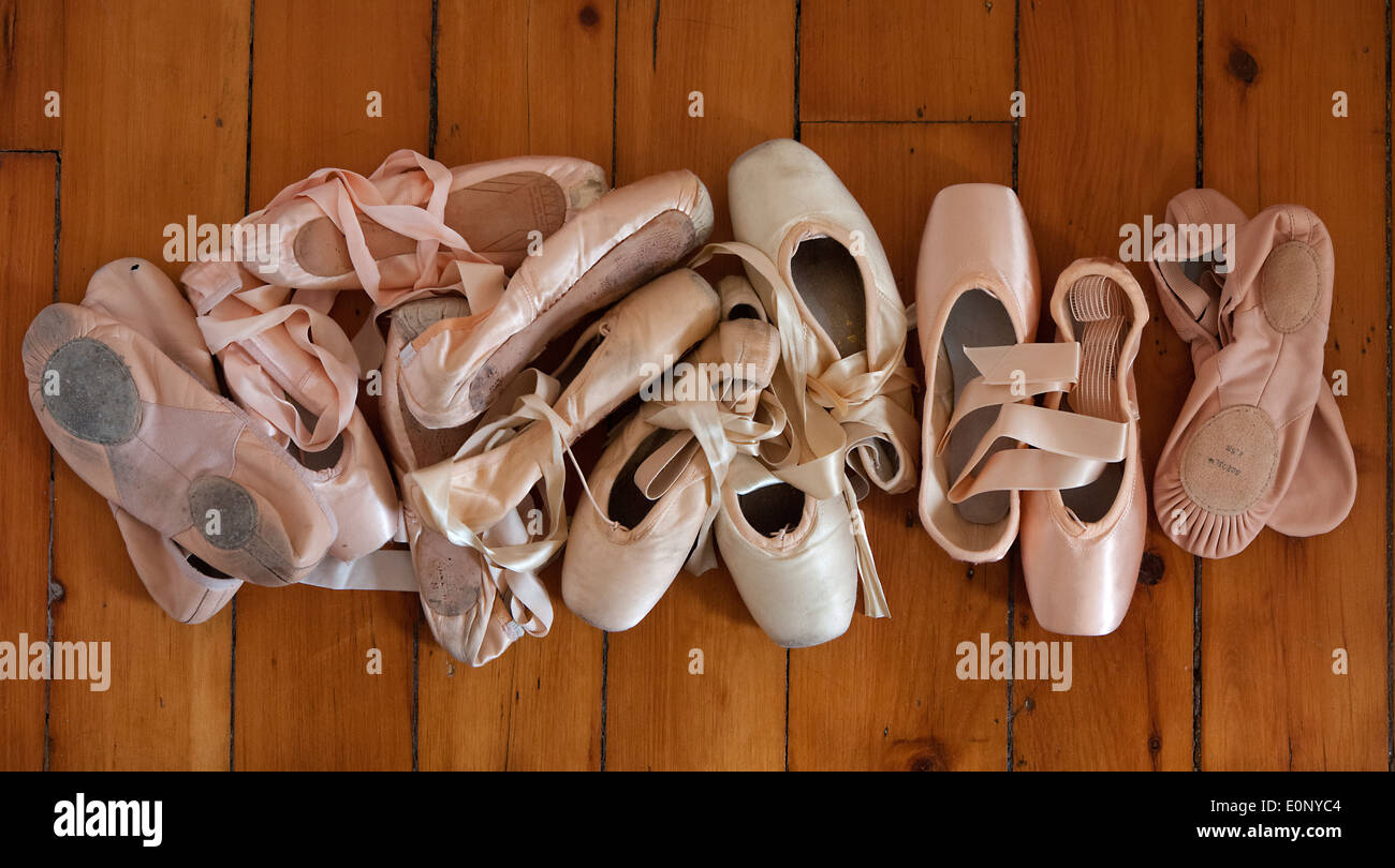 pile of ballet shoes and pointe shoes on a wood floor - Stock Image