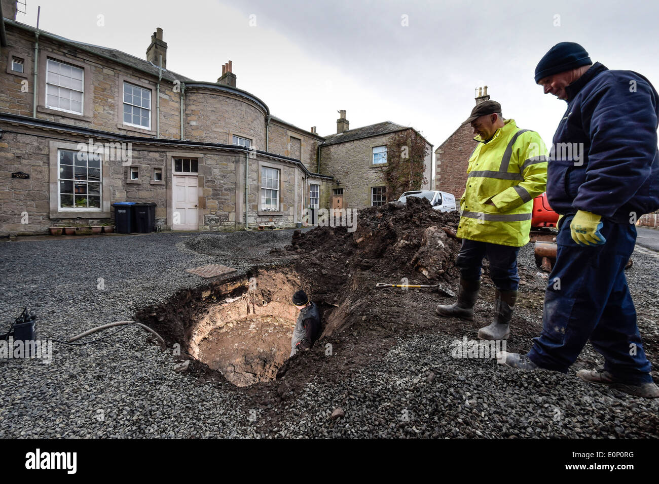 Builders inspect a hidden underground structure revealed by a void collapsing in a yard - Georgian brick icehouse, well or drain - Stock Image